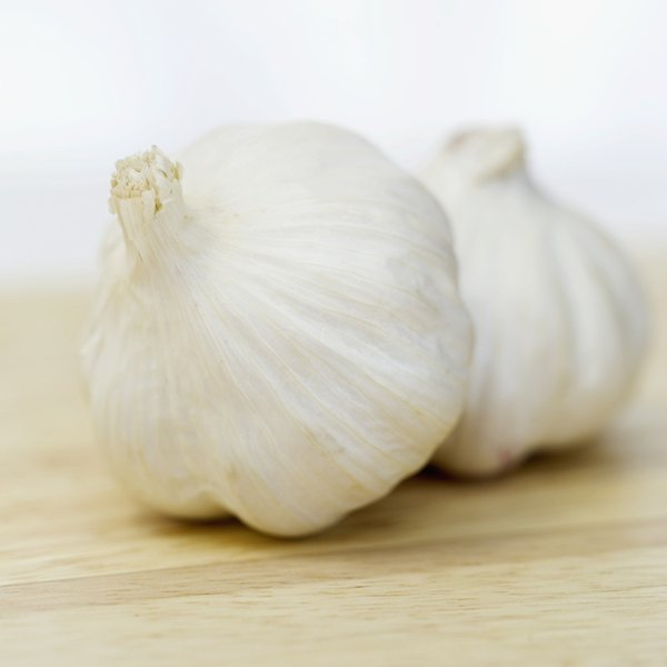 Two large garlic cloves on a counter.