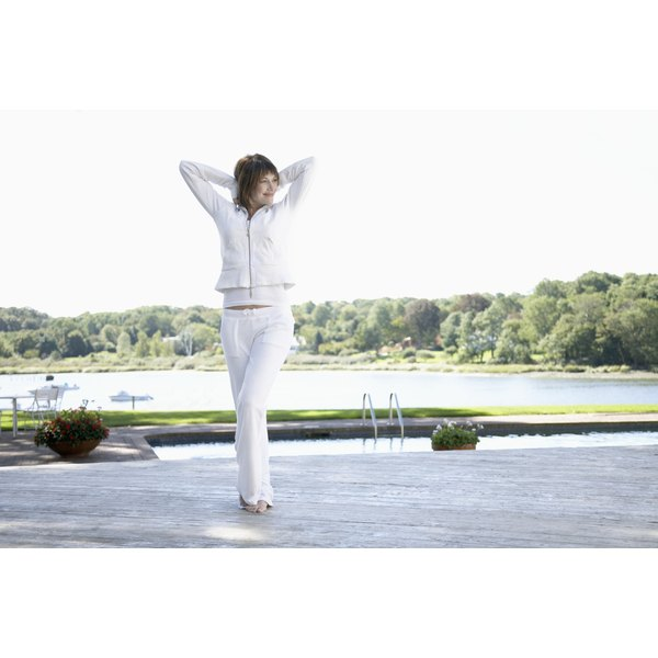 A woman wearing white pants stands, stretching near a pool.