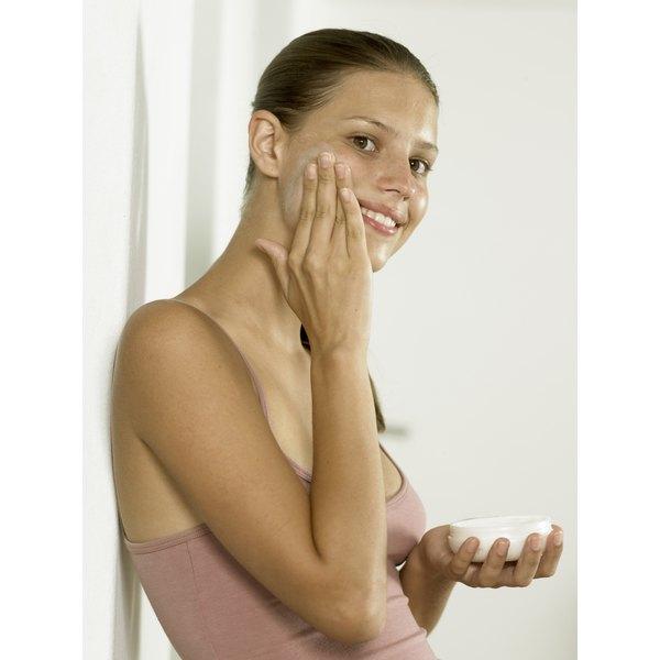 Young woman applying facial cream to her cheek.