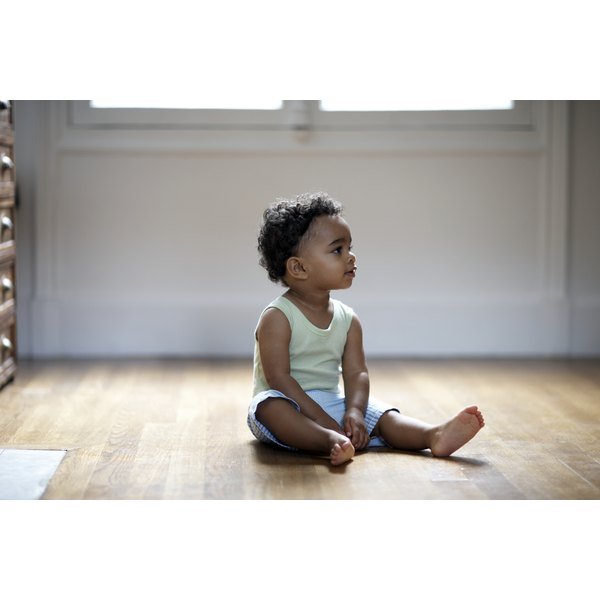A two year old sitting on the floor of her home.