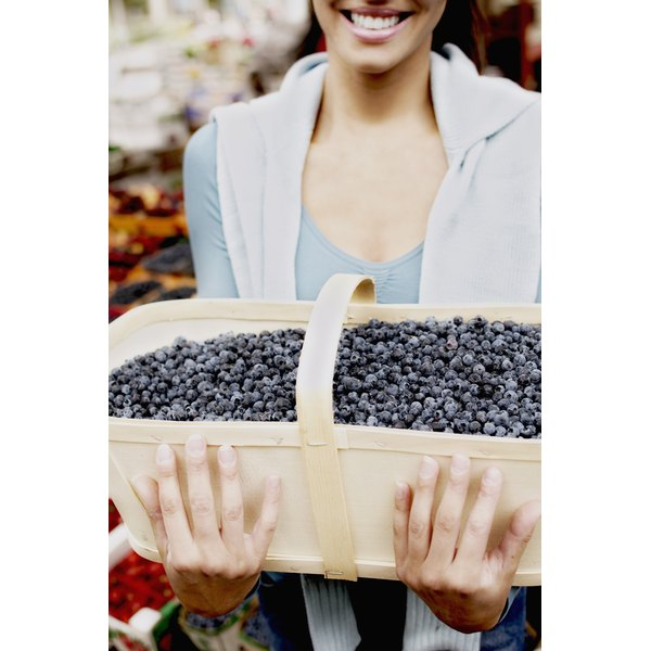 close up of woman holding large basket of blueberries with both arms