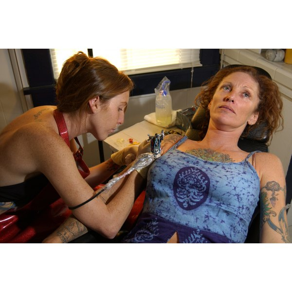 A woman is getting a tattoo.