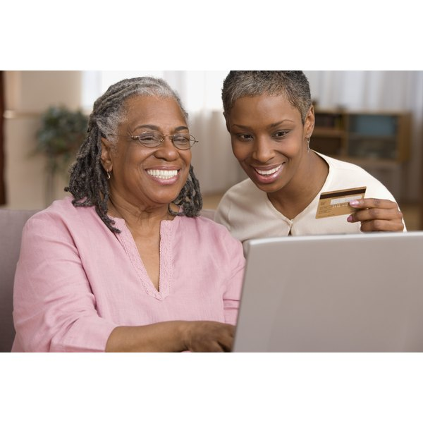 A woman and her mother are holding a credit card and sitting in front of a computer.