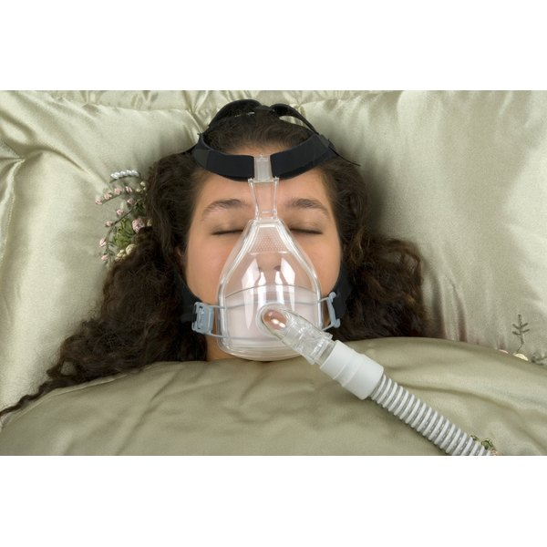 A woman is sleeping with a CPAP machine.