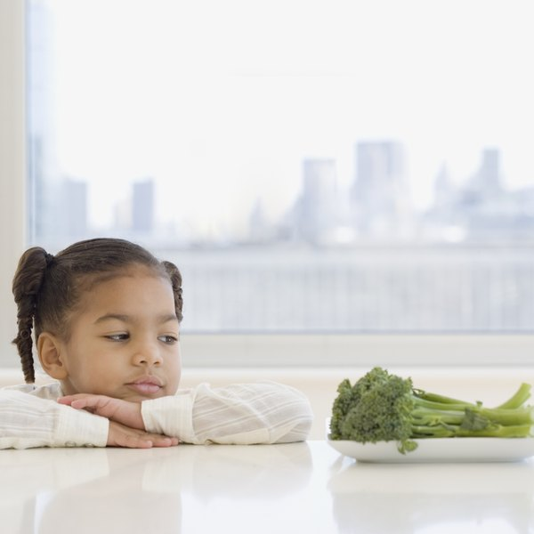 A young girl sitting at a table looking at vegetables.