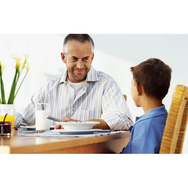 A mature man is sitting at a table with his son and a glass of milk.
