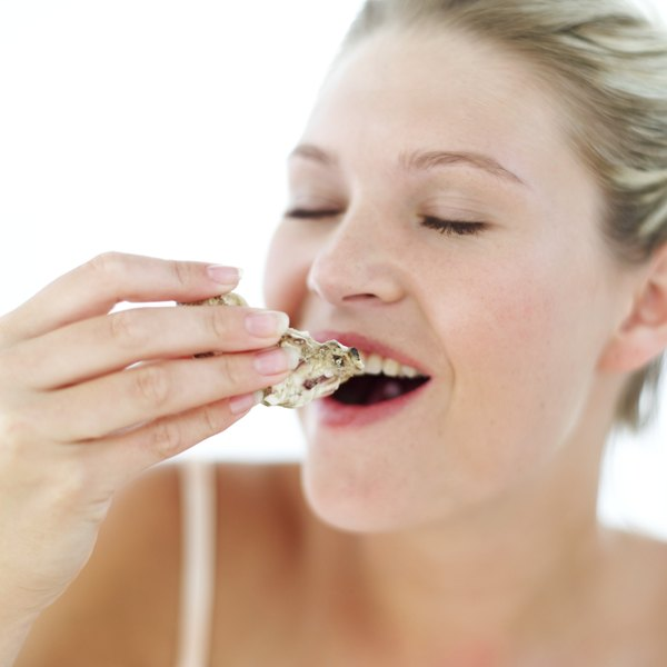 Young woman smiling about to eat an oyster.