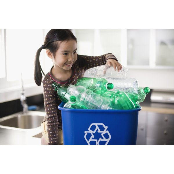 A girl recycling plastic bottles at home.