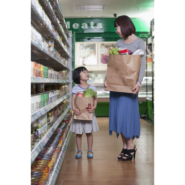 Mother and daughter holding grocery bags in market in Beijing.