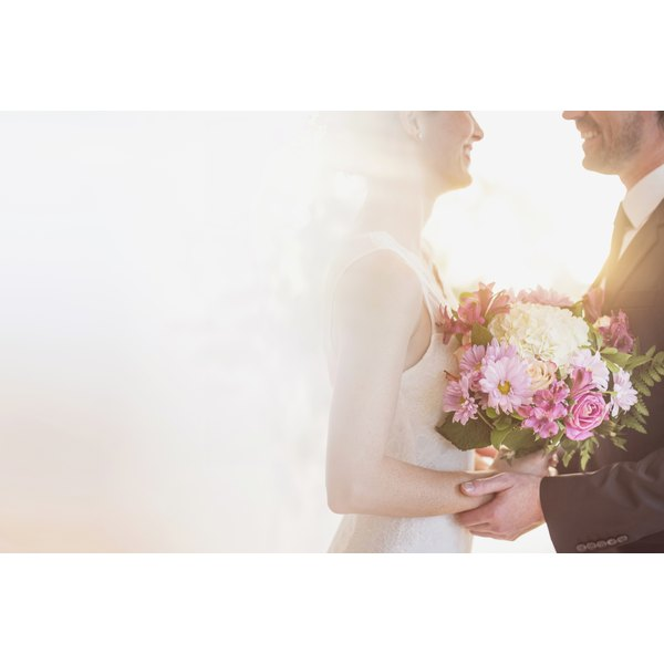 A bride and groom in sunlight on their wedding day.