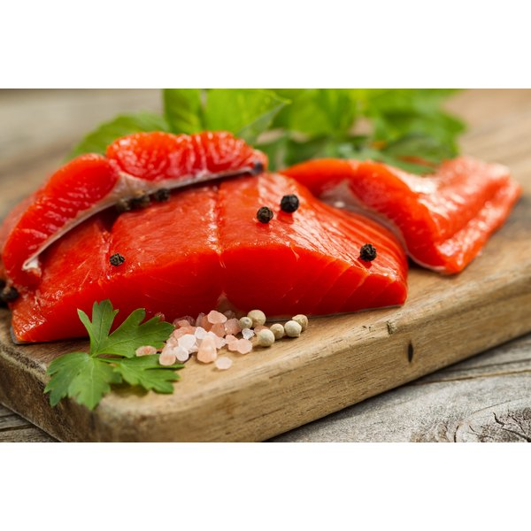 A filet of salmon on a chopping board.