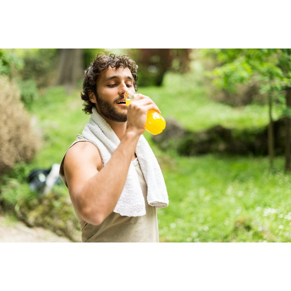 A man is drinking a sports supplement.