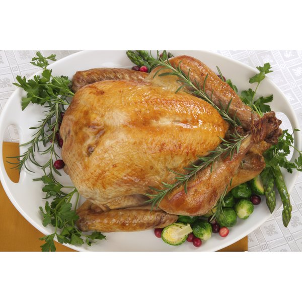 Roasted and garnished whole turkey on a large serving plate.