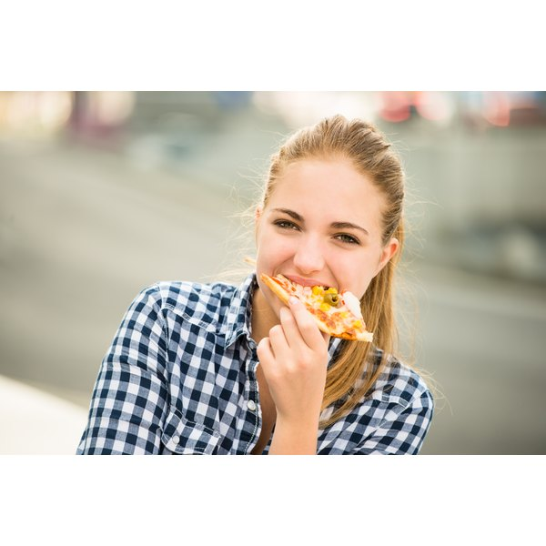 A woman eats pizza as a healthy lunch idea.