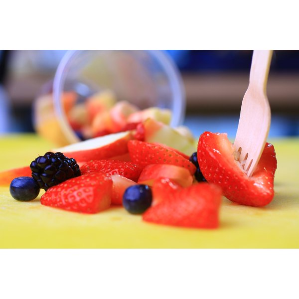 A close-up of a plastic fork picking up sliced strawberries, among blueberries and blackberries.