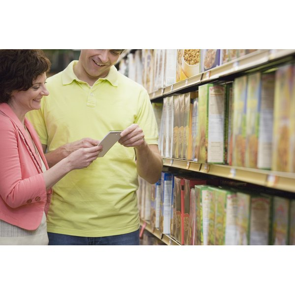 A man and a woman looking at a list in the cereal aisle of a store.