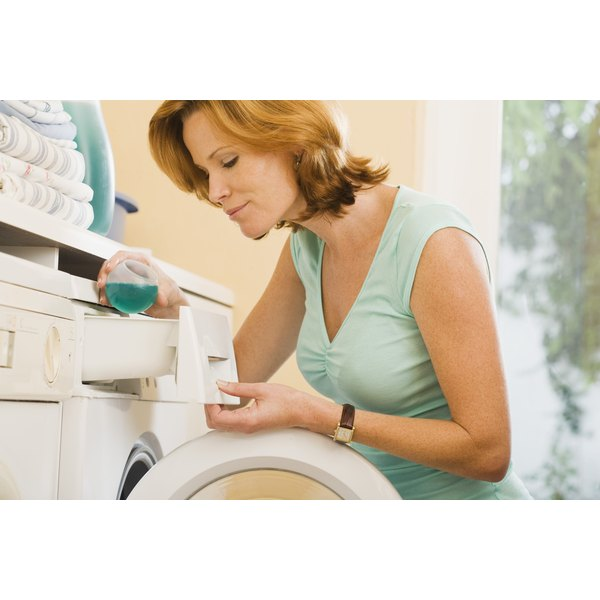 A woman adding laundry detergent into a machine