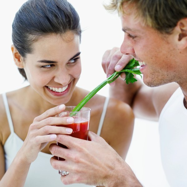 A couple enjoy a glass of tomato juice.