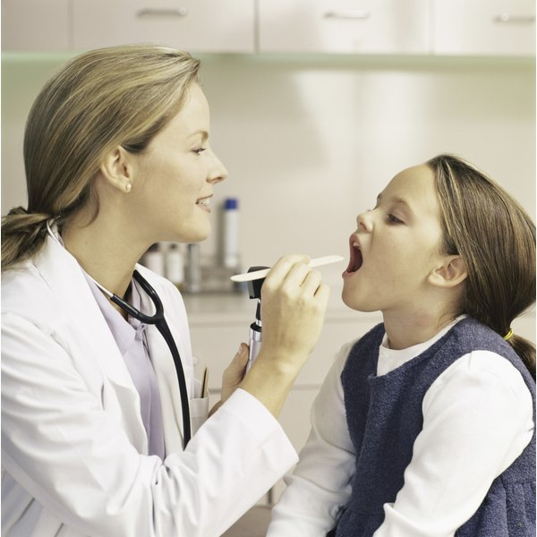 Doctor examines a young girl's throat.
