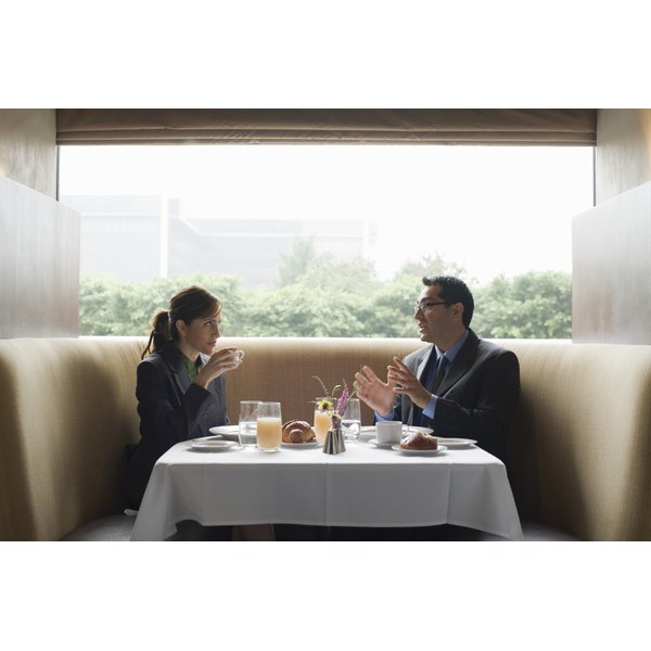 Two collegues having a conversation in a restaurant booth.