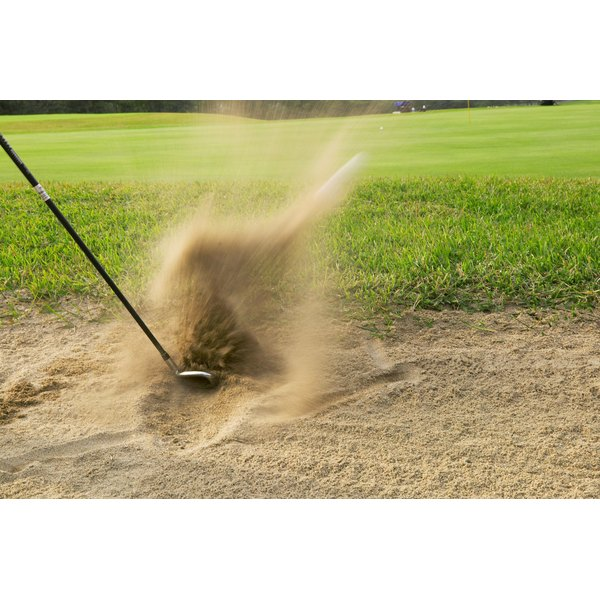 Someone is swinging a golf club in a sand pit.