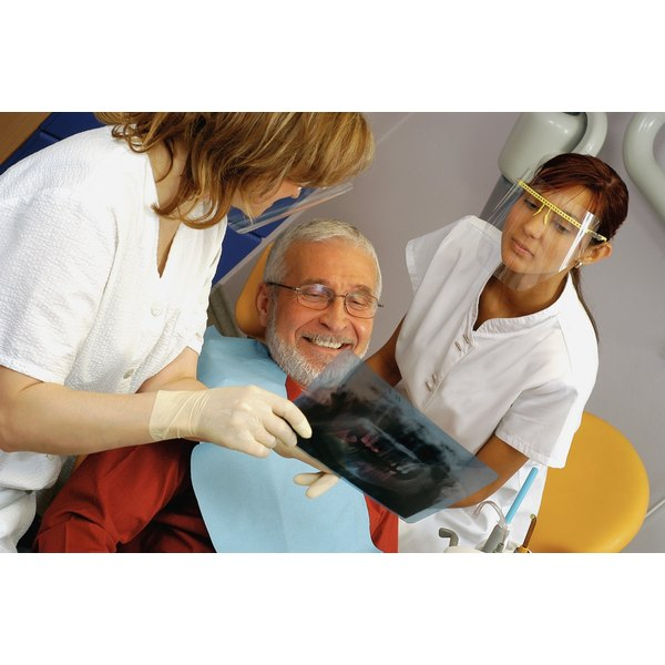 Two dentists are showing x-rays to a patient.