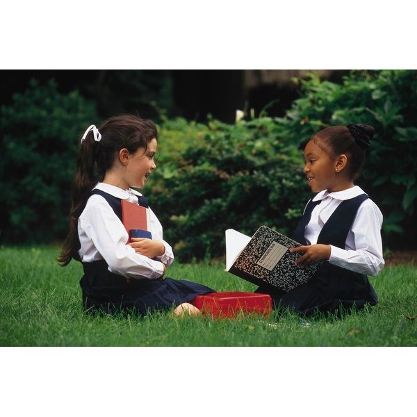 Two young girls in school uniforms studying on the grass.