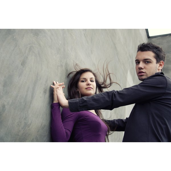 A young woman holdig hands with her boyfriend against a wall.