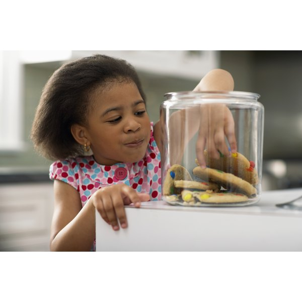A young girl is reaching in to the cookie jar.