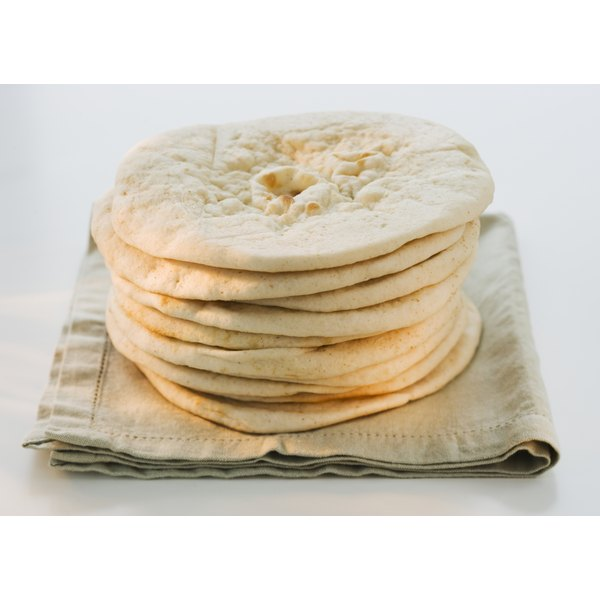A stack of pita bread on a kitchen towel.