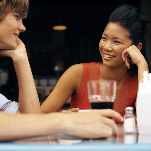 A young couple enjoy a cola over a discussion.