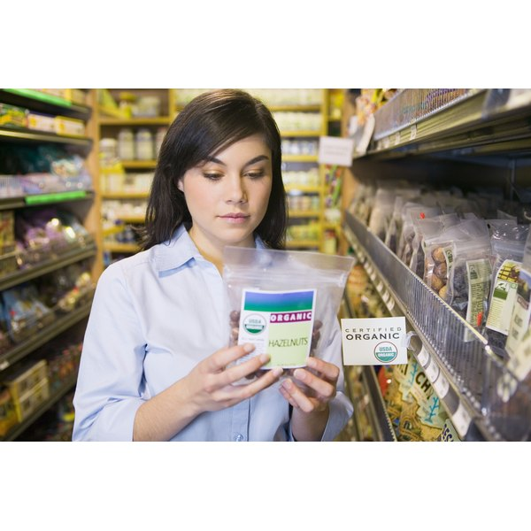 Young woman reading a label of food packet in grocery store.