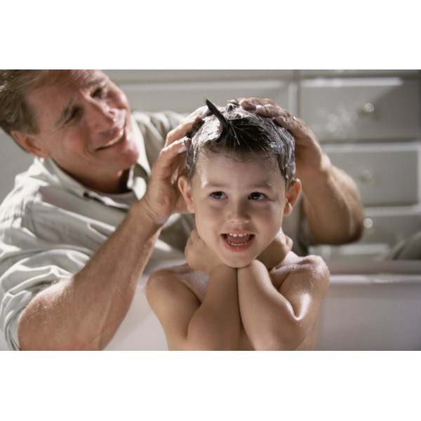 A father is shampooing his son's hair.