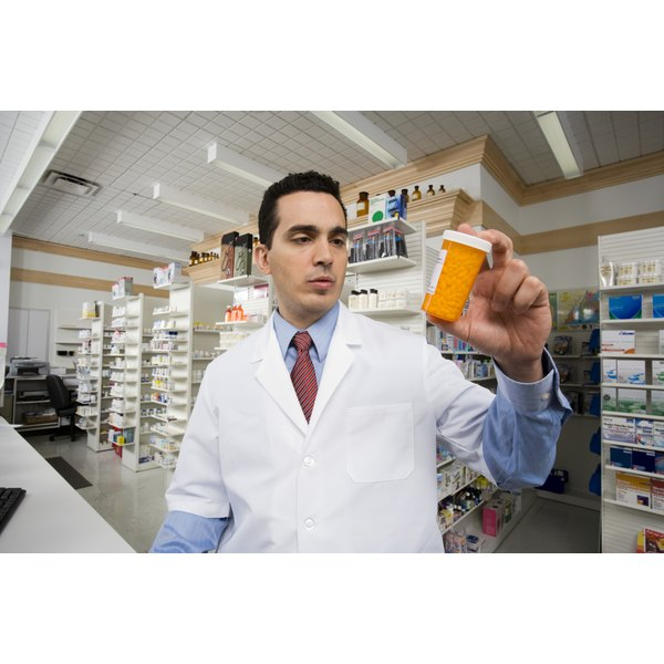 A pharmacist holds up a bottle of pills.