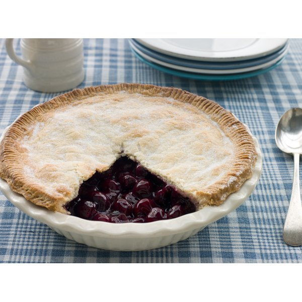 A whole cherry pie with a missing slice on a tablecloth.