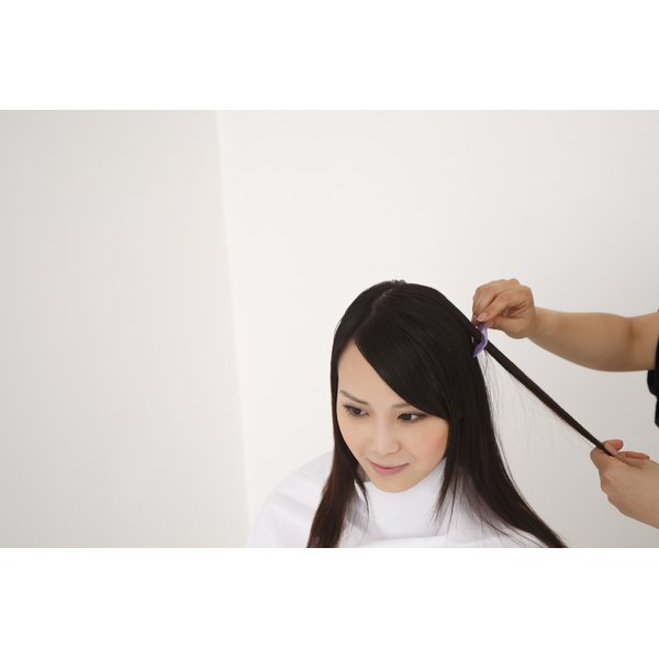 Young woman having her black hair styled.