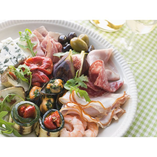 An antipasto platter containing greens, cured meats and pasta.