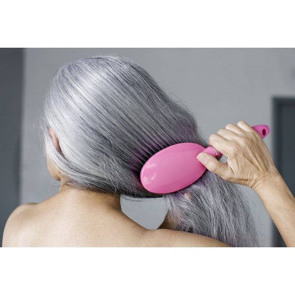 A mature woman brushes her gray hair with a hairbrush.