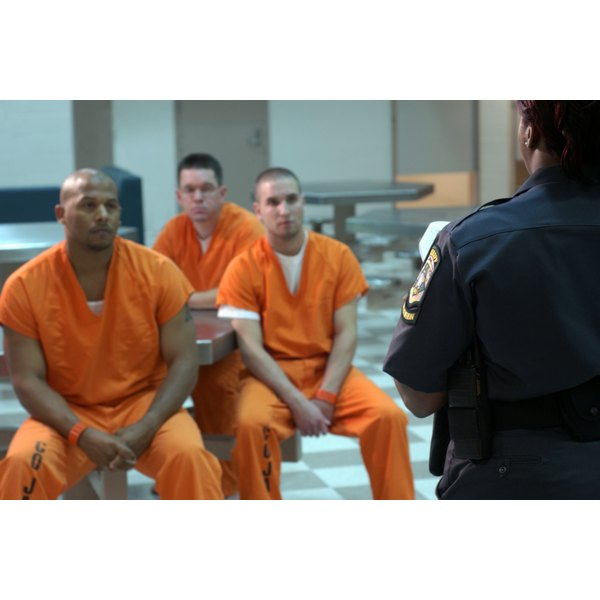 Three men sitting in jail dressed in orange jumpsuits.