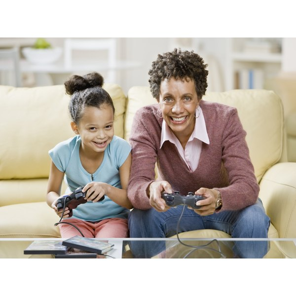 A mother and daughter are playing a video game together.