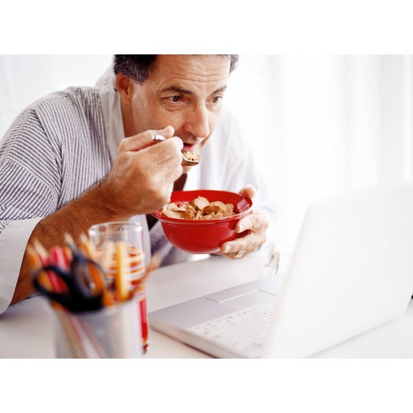 A man eating a bowl of cereal in his home office.