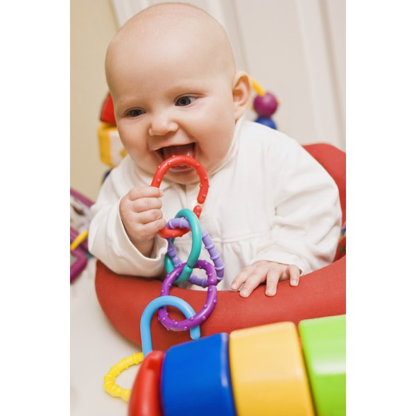 Baby putting rings in mouth.
