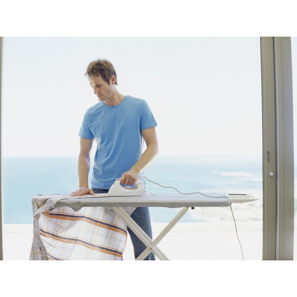A man is ironing a shirt.