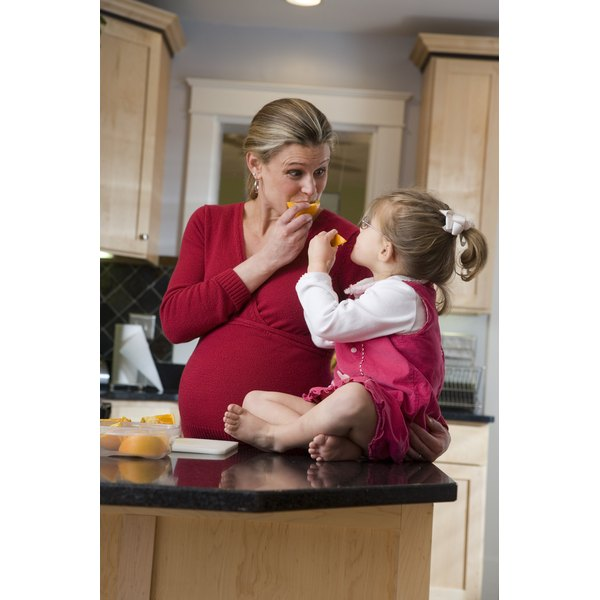 Pregnant woman eating oranges with her daughter