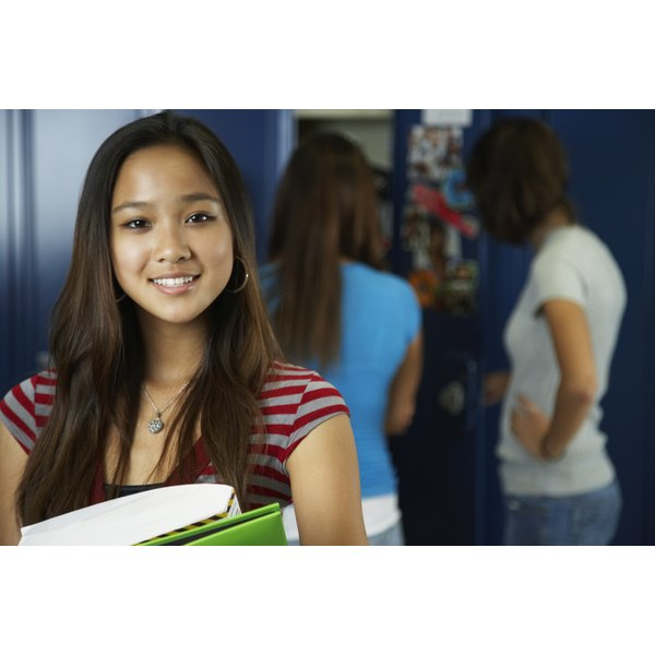 A teenage girl looks at the camera as her friends in the background are at their school lockers.