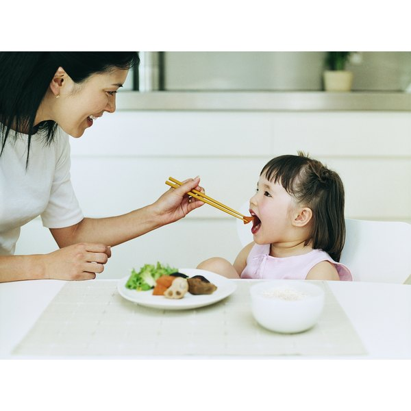 Japanese mother feeds her daughter with chopsticks.