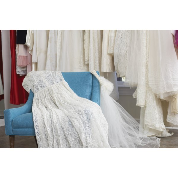 Wedding dress laying on top of chair.