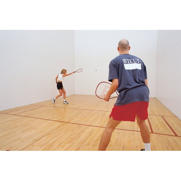 A couple playing racquetball on an indoor court.
