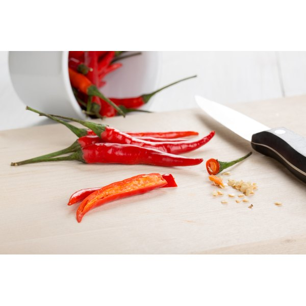 Cayenne peppers on a cutting board with a knife.