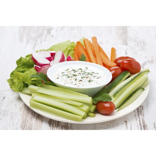 A large plate of healthy dip and vegetables on a wooden table.